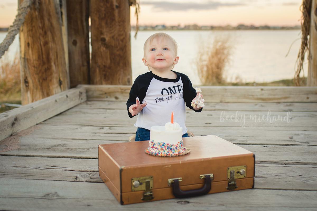 A little boy eats cake on the dock by Windsor Lake