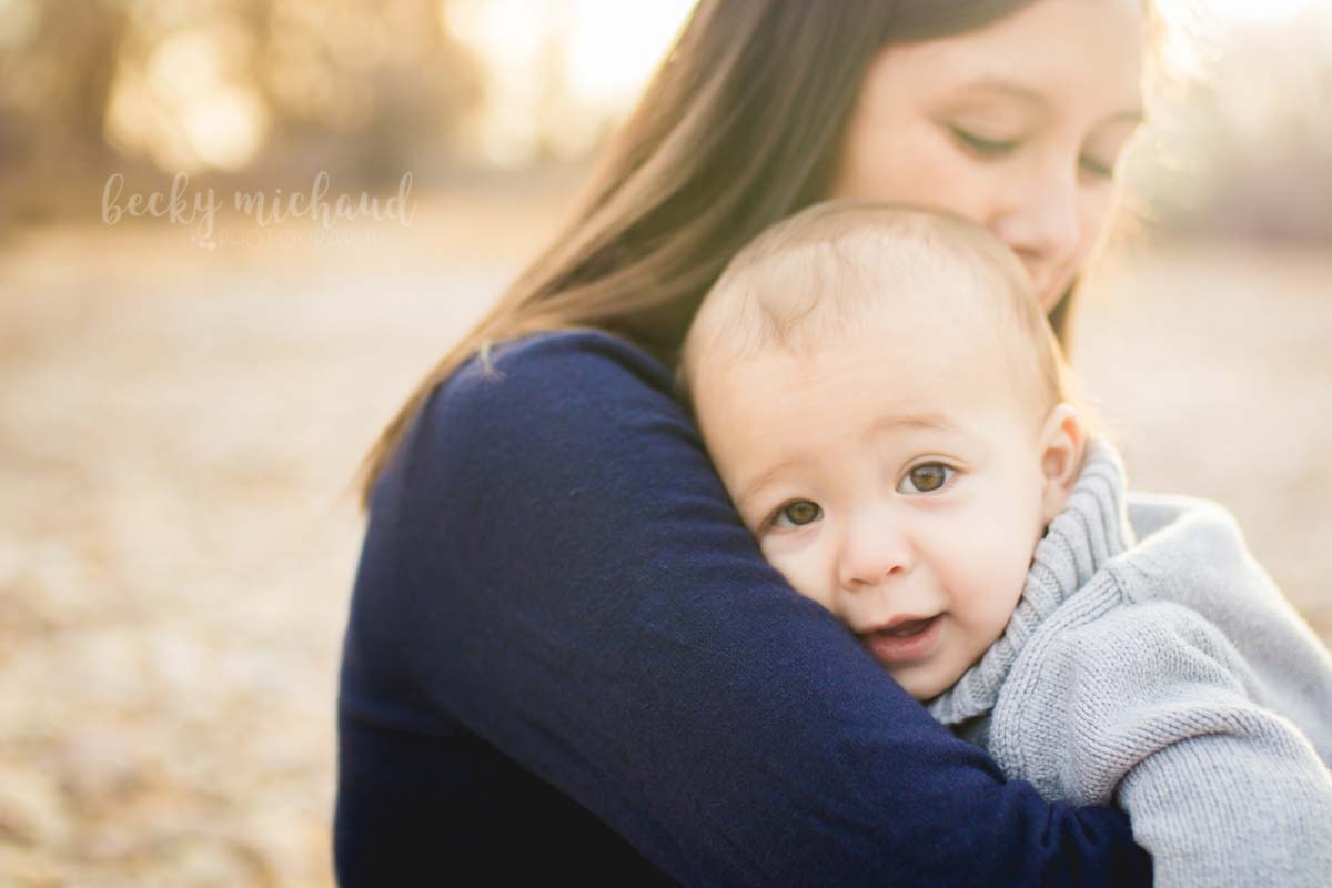 Baby boy snuggles into his mom's shoulder and looks at the camera