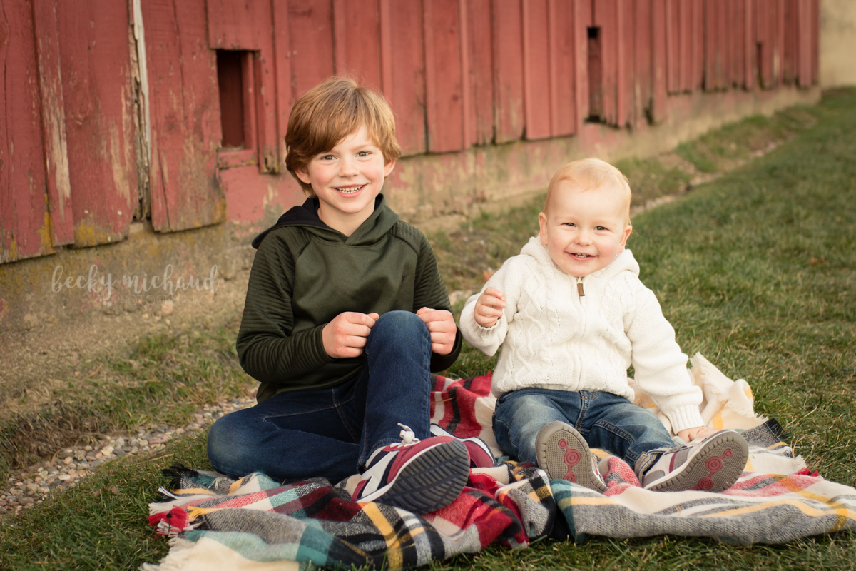 Brothers pose on a plaid blanket in front of a red barn in south Fort Collins, CO