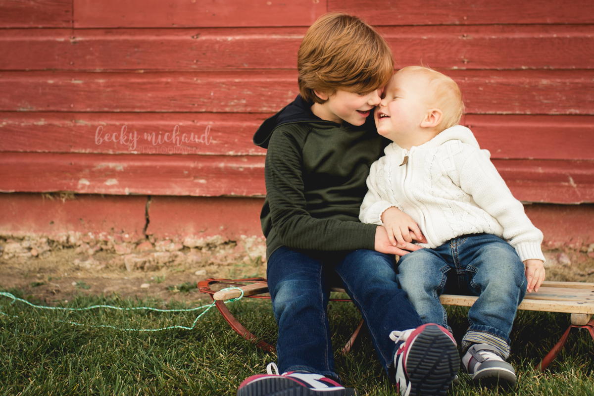 two brothers rub noses together while sitting on an antique wooden sled