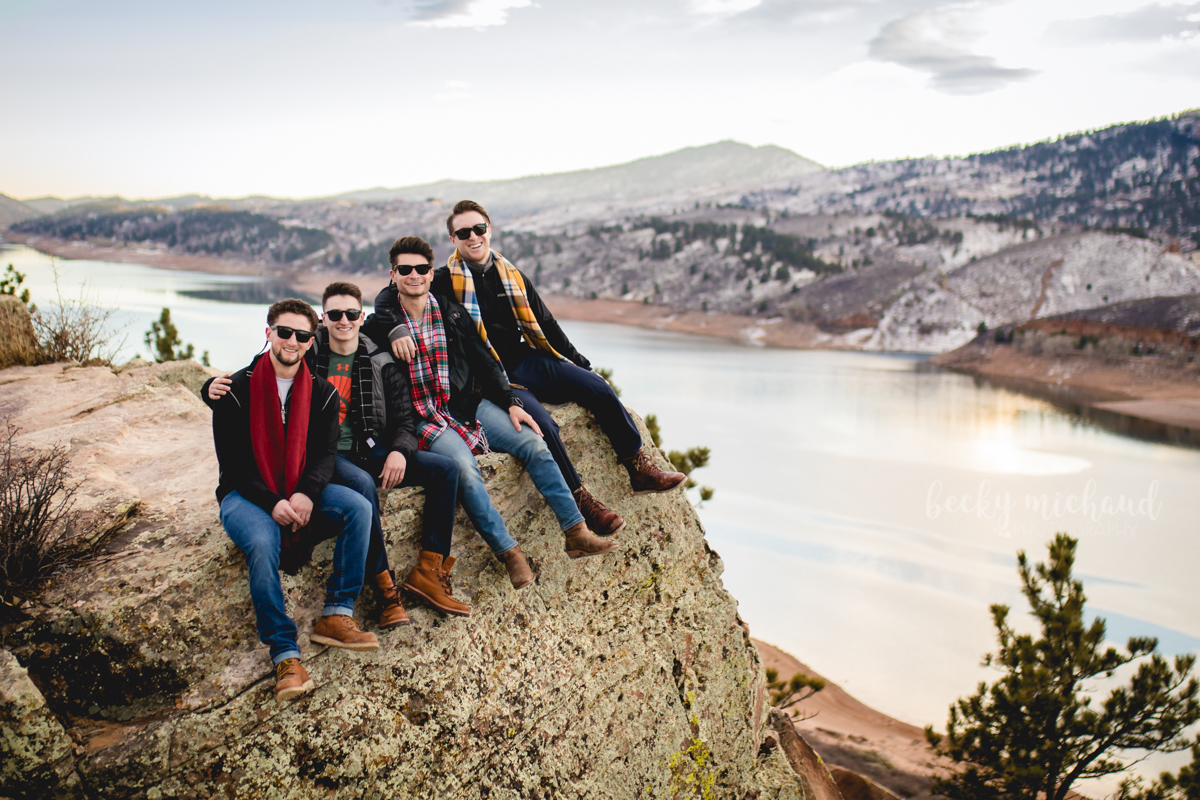 Four brother sit on a cliff as the sunsets over Horsetooth Reservoir in Fort Collins, CO