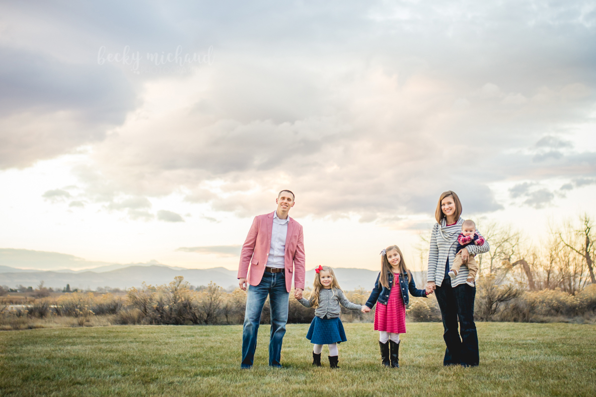 A family of five stands in a field with the Colorado mountains behind them