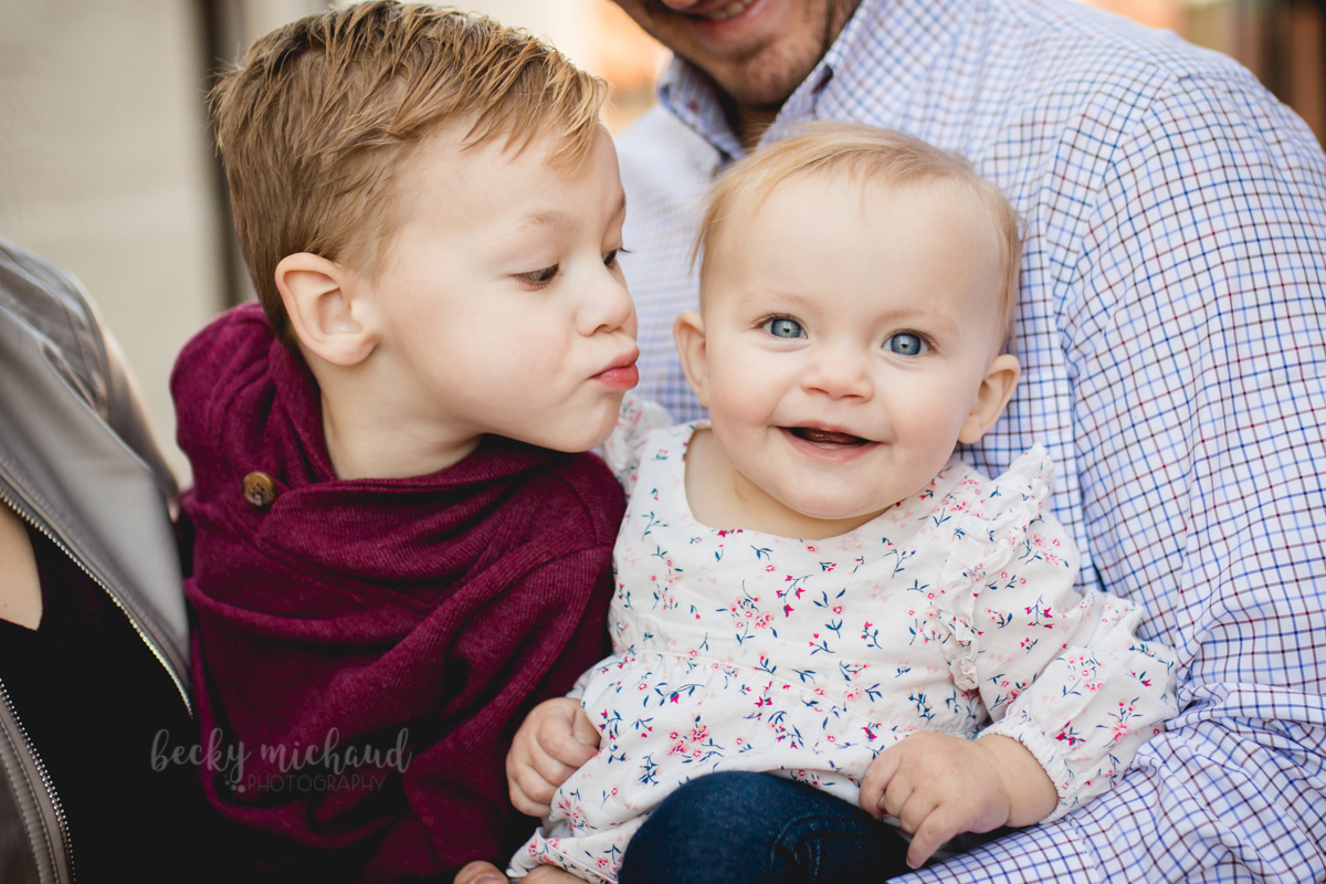 A little boy reaches to kiss his baby sister on the cheek