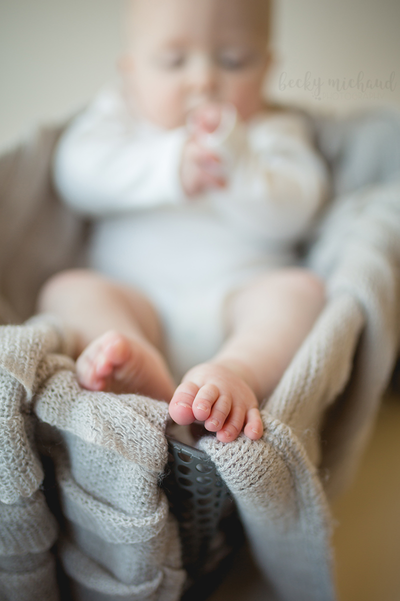 Baby toes on a grey blanket in a basket