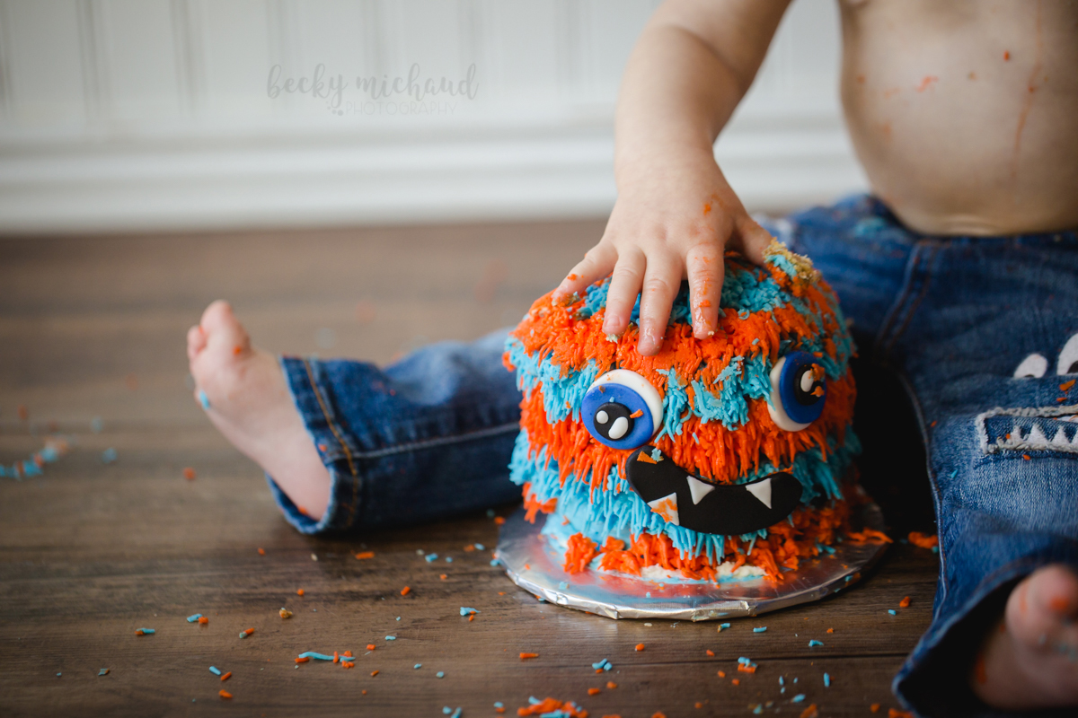 Close up photo of a little hand digging in to cake during a cake smash photo session for a one year old