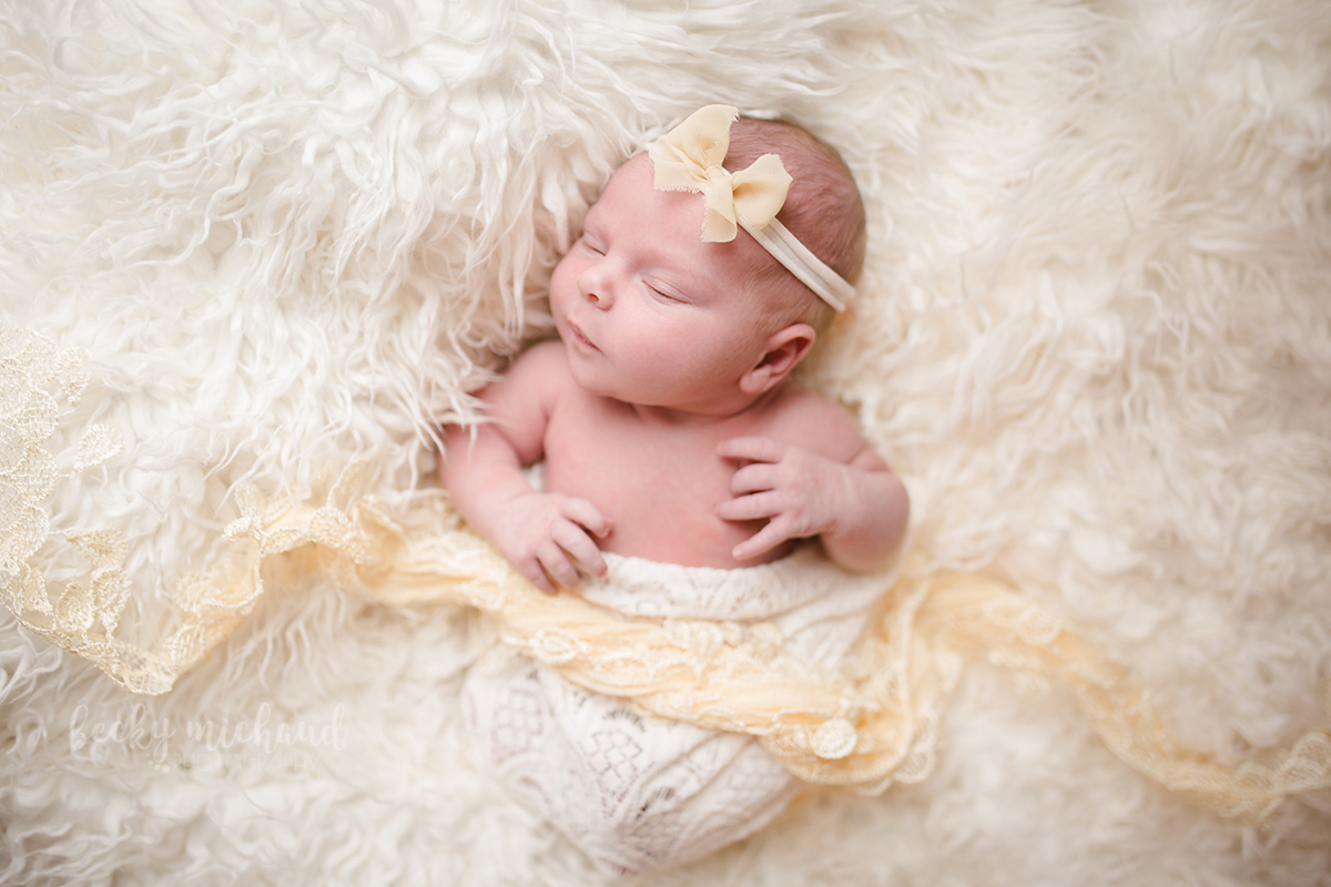 Newborn baby on a cream colored fur with a yellow bow