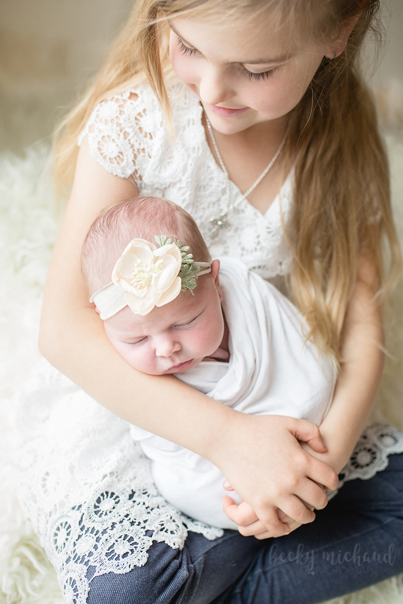 A big sister looks down at her new baby sister as they pose for a photo taken by Becky Michaud, Fort Collins newborn photographer
