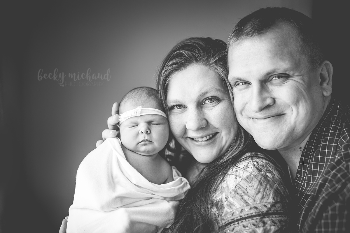Parents hold their newborn baby girl during their in home photography session in Northern Colorado