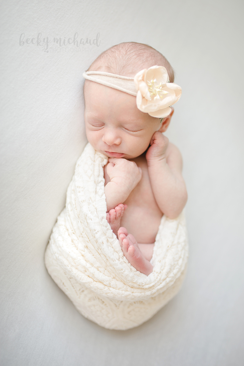 Simple natural newborn photo of a baby girl with a flower headband taken by Becky Michaud, Fort Collins newborn photographer