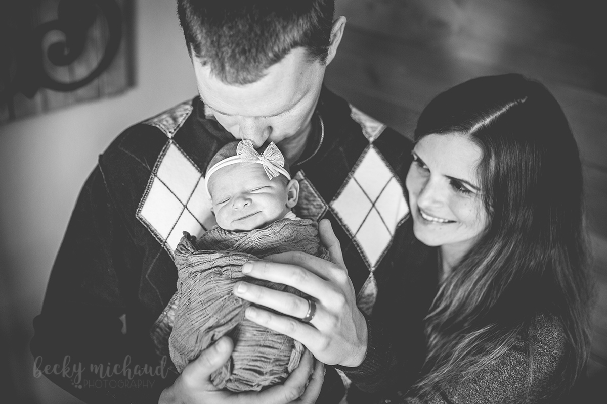 black and white photo of a family of three posing for their in home newborn photo session