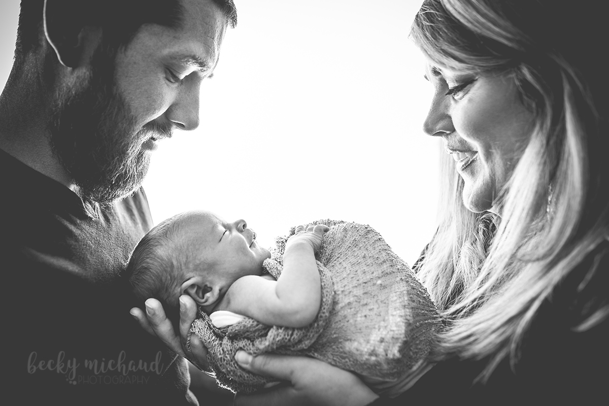 a new mom and dad hold their baby between them while he smiles during their in home newborn photo session
