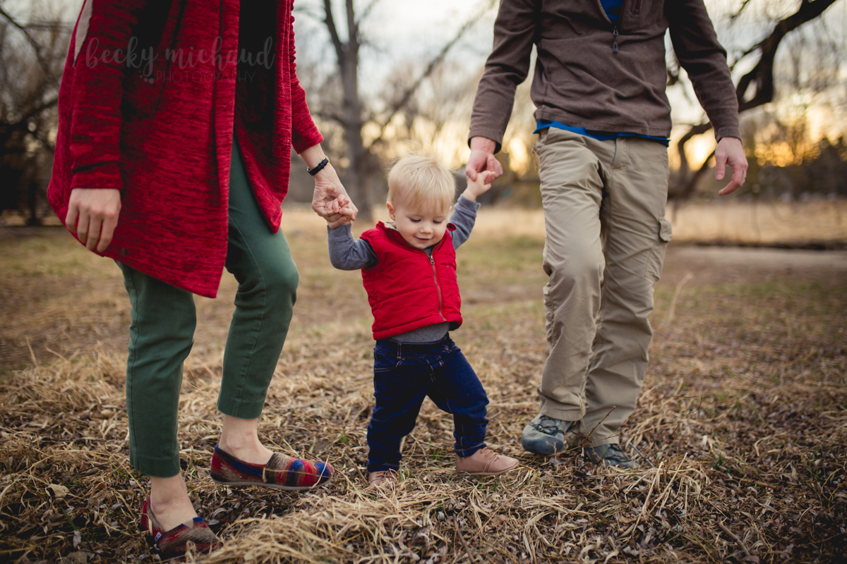 A baby boy practices walking while holding his parents' hands near Spring Creek Trail in Fort Collins, Colorado