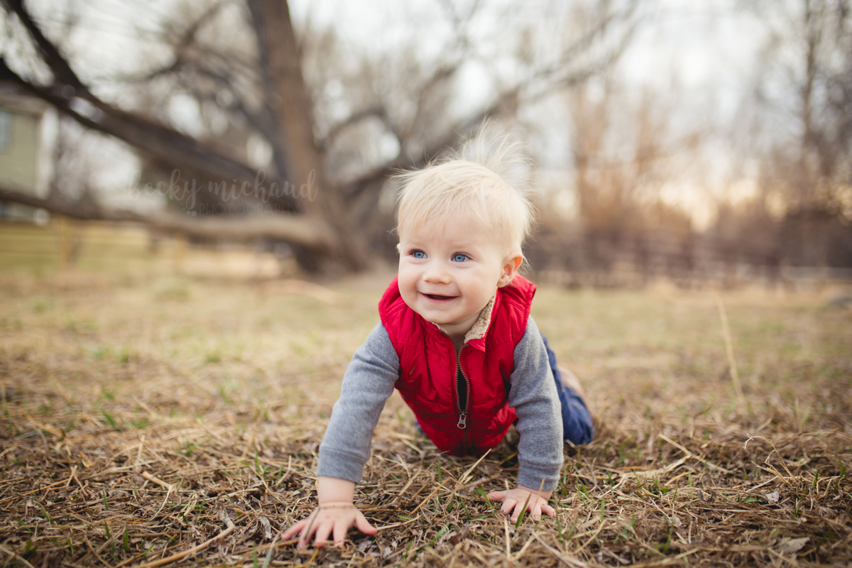 A baby boy crawls in the grass during his Fort Collins one year photo session