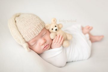 A newborn baby wearing a knit slouch hat holds a felted wool teddy bear
