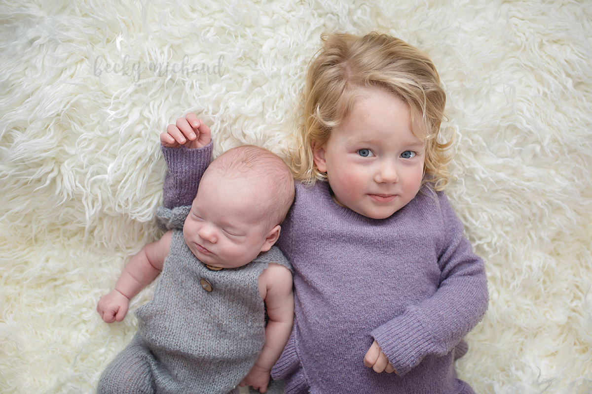 A big sister holds her baby brother