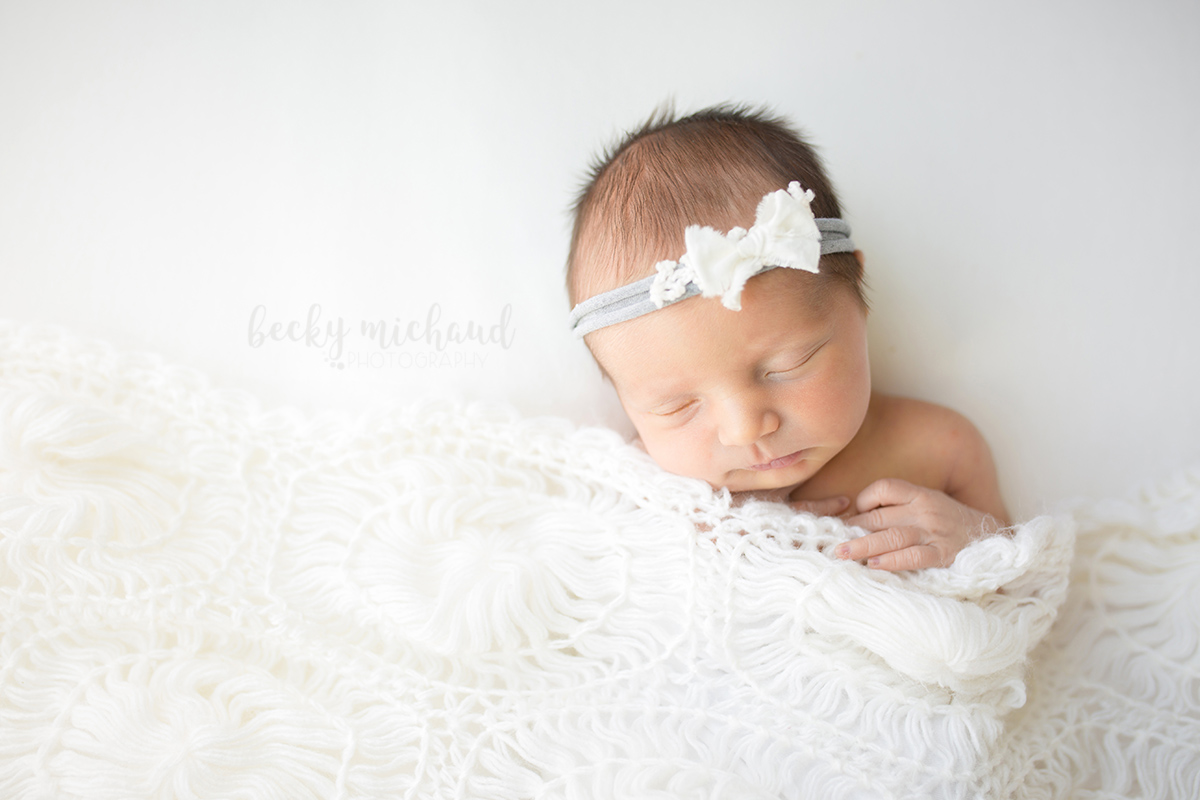 Newborn portrait taken in Loveland Colorado of a baby girl tucked under a white blanket