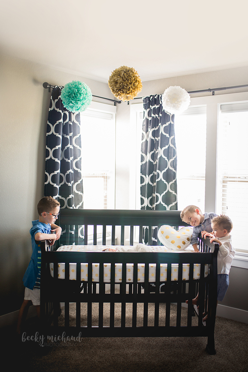 Three boys peek at their baby sister in her crib in their Loveland, Colorado home
