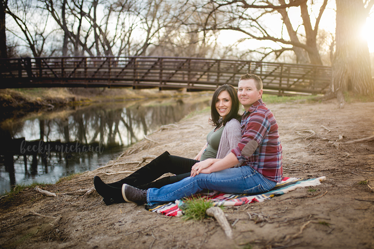 Maternity photo taken at Legacy Park in Fort Collins Colorado of a couple sitting on a blanket by a bridge