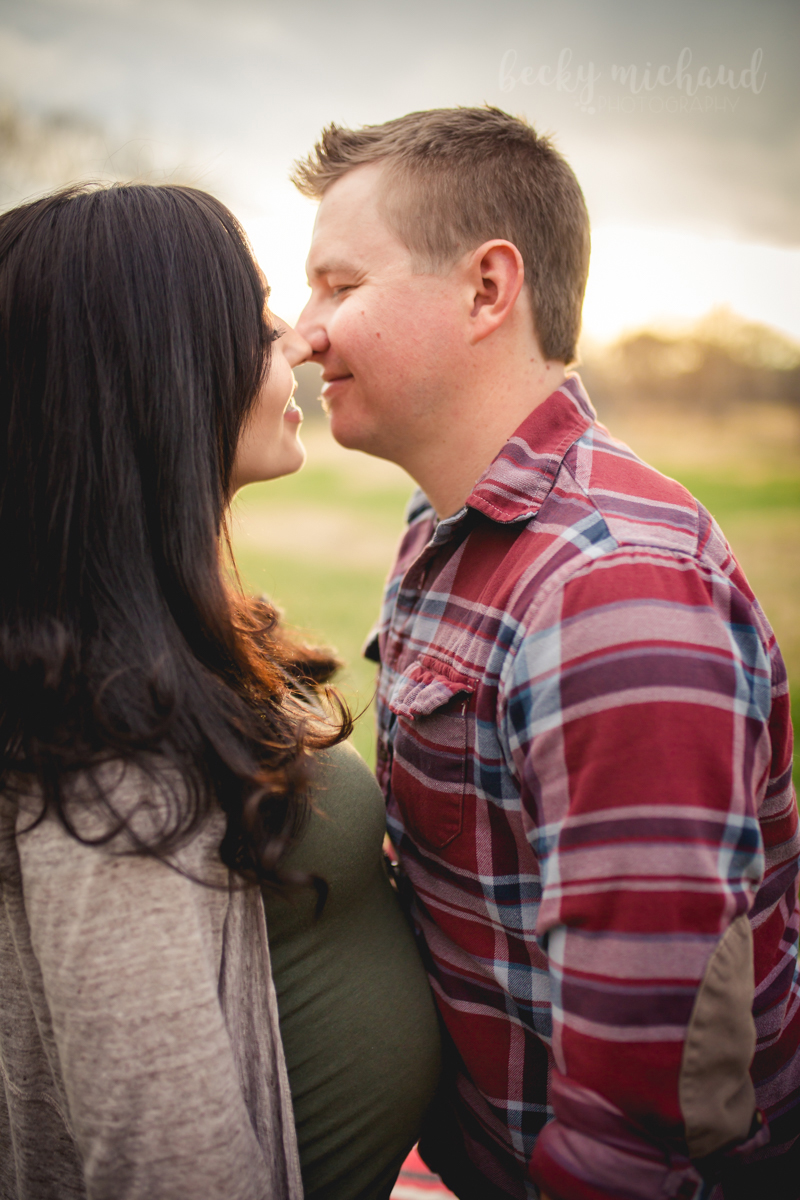 A couple goes in for a kiss during their maternity photo session with Becky Michaud, Fort Collins Photographer