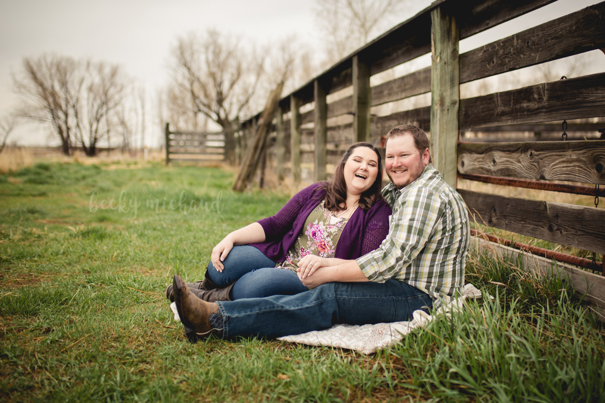 A couple laughs together while sitting by a fence during their photo session at Sandstone Ranch in Longmont Colorado