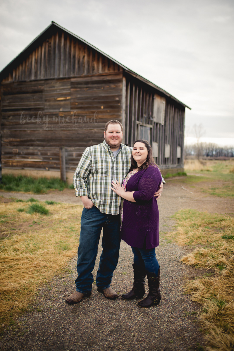A couple poses in front of a wooden barn at Sandstone Ranch