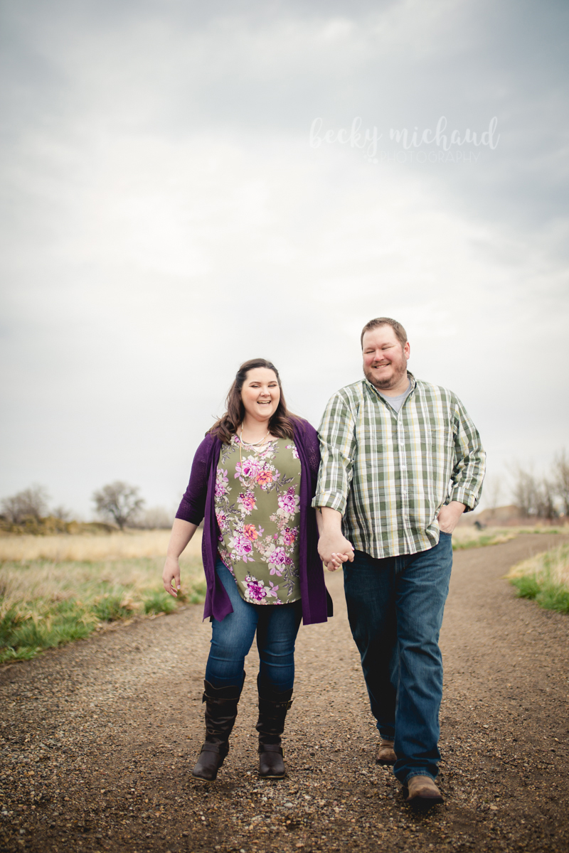 A man and woman walk down a path laughing together during their engagement photo shoot