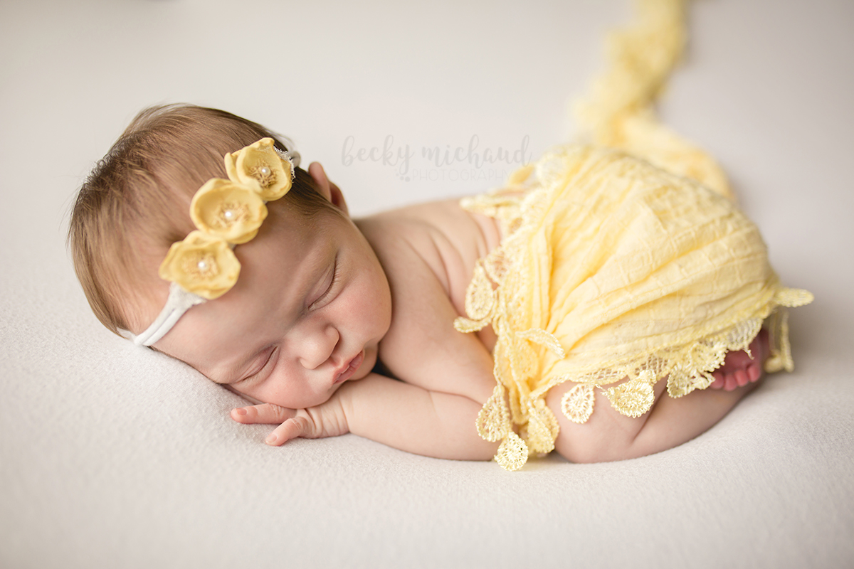 A newborn girl dressed in yellow curls up on a white backdrop during her photo session with Fort Collins photographer, Becky Michaud