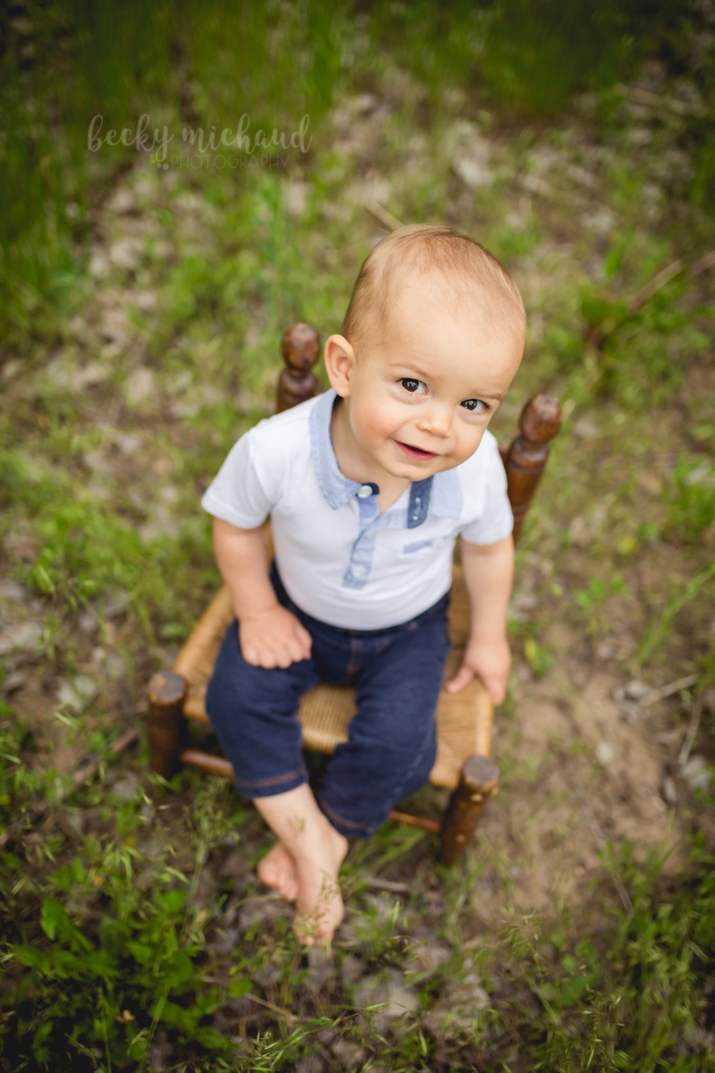 A little boy sitting on a wooden chair looks up the camera during his Fort Collins one year photo session