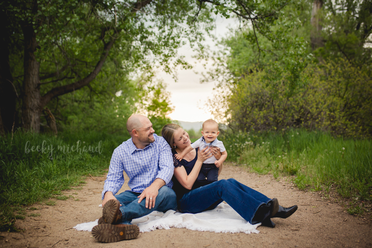 A family of three poses for their Fort Collins photographer by playing together in the woods