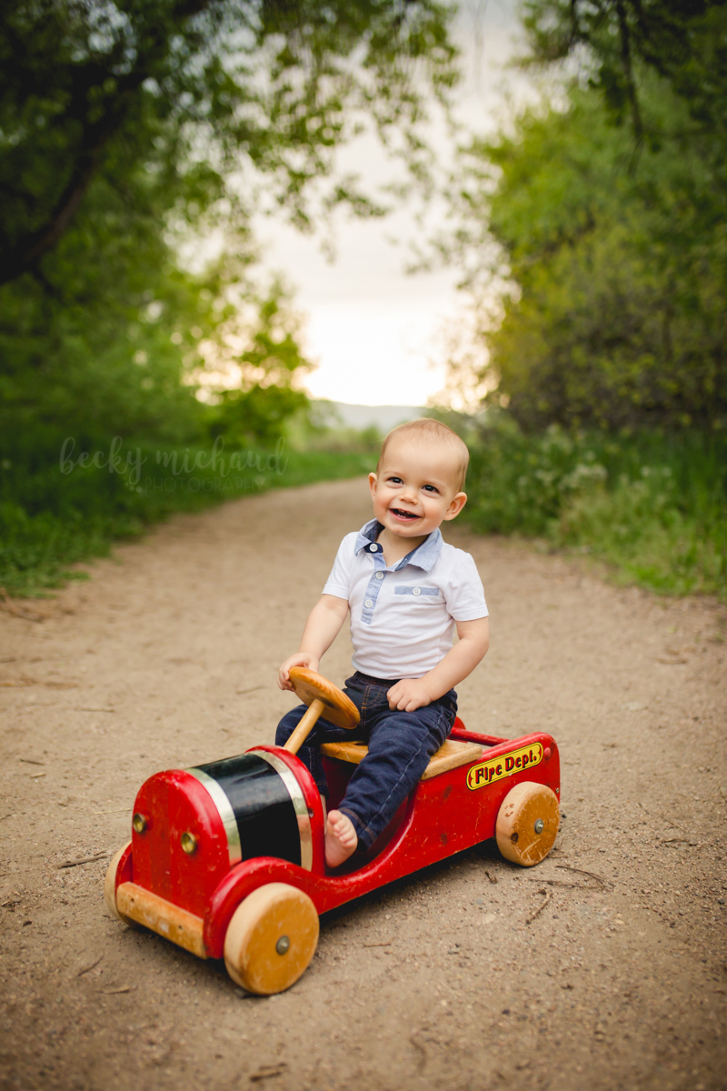 A one year old boy rides a wooden fire truck at a Fort Collins Natural Area