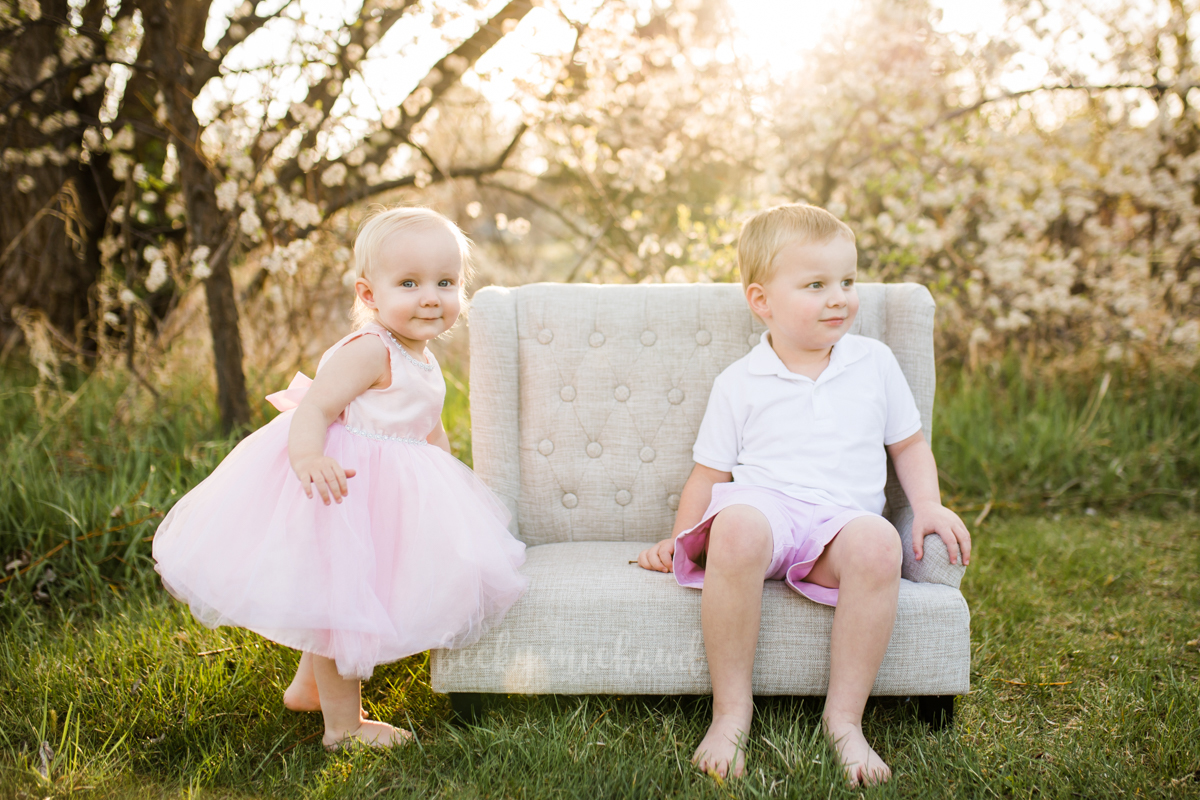 Two siblings play on a little white couch while having their photos taken by Becky Michaud, Fort Collins photographer