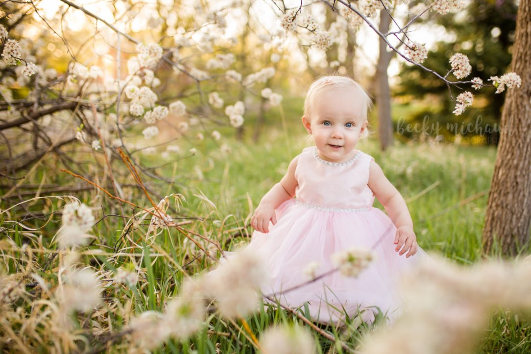 A baby girl peeks at the camera through the white flowers during her one year photo session