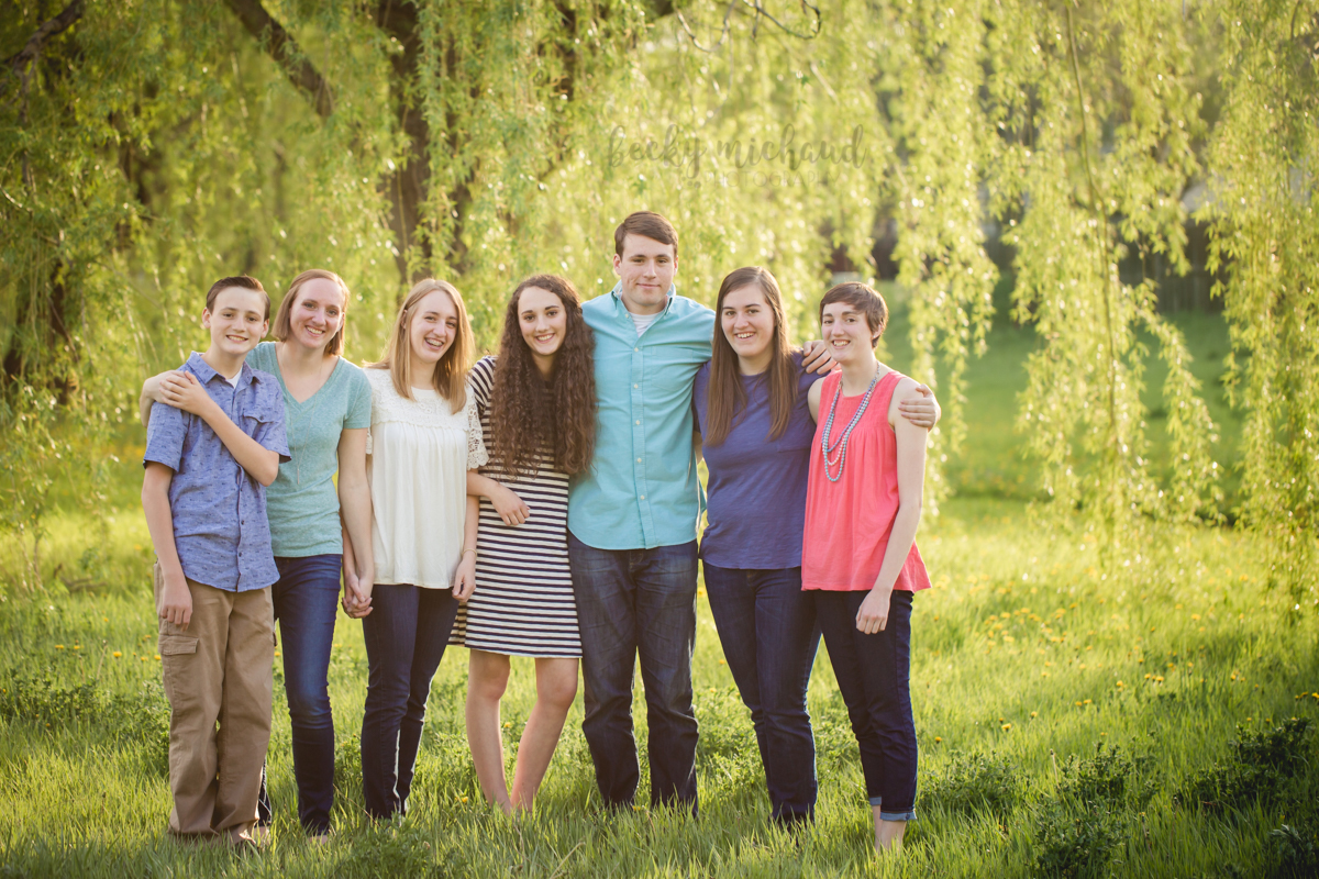 A group of siblings poses together by the willow trees for their photography session with Becky Michaud