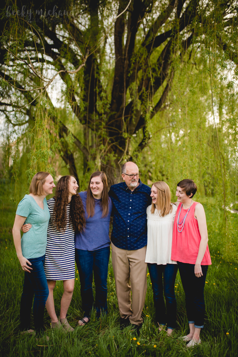 A group of sisters poses with their dad near a large willow tree in southeast Fort Collins