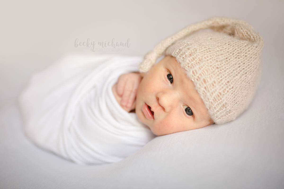 Newborn photo by Becky Michaud, Fort Collins photographer, of a baby on a white backdrop with wide open eyes