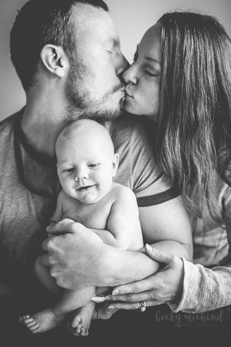 Two parents kiss while embracing their new baby during their in home lifestyle photo session