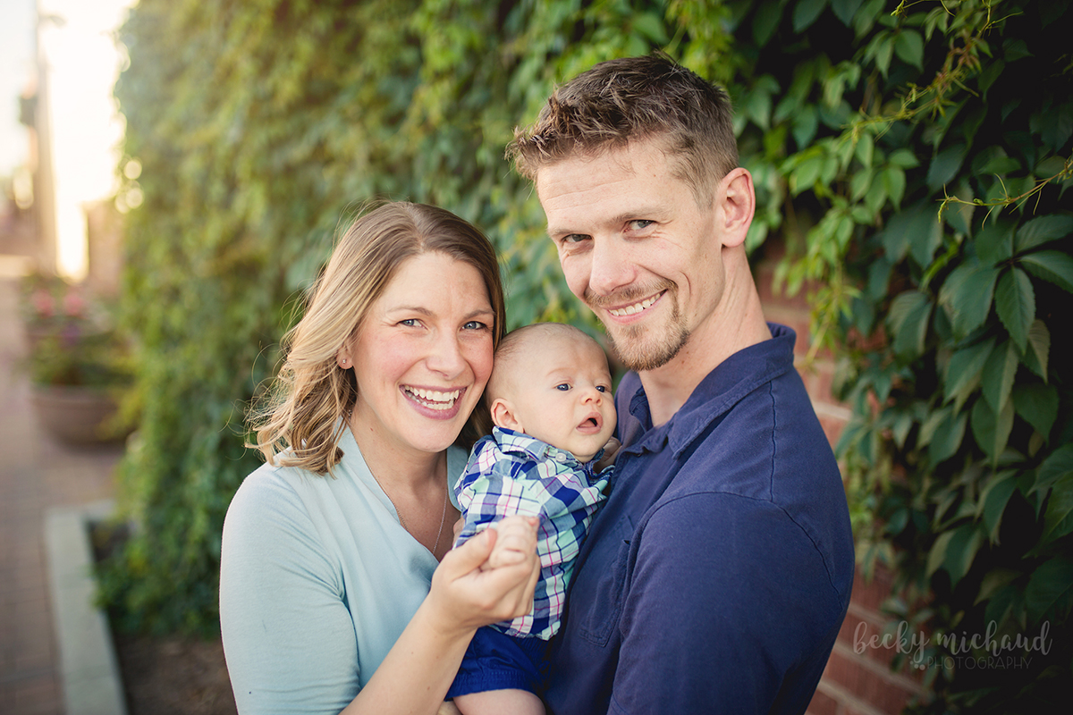 A family of three smiles together in front of a wall of ivy in Old Town, Fort Collins