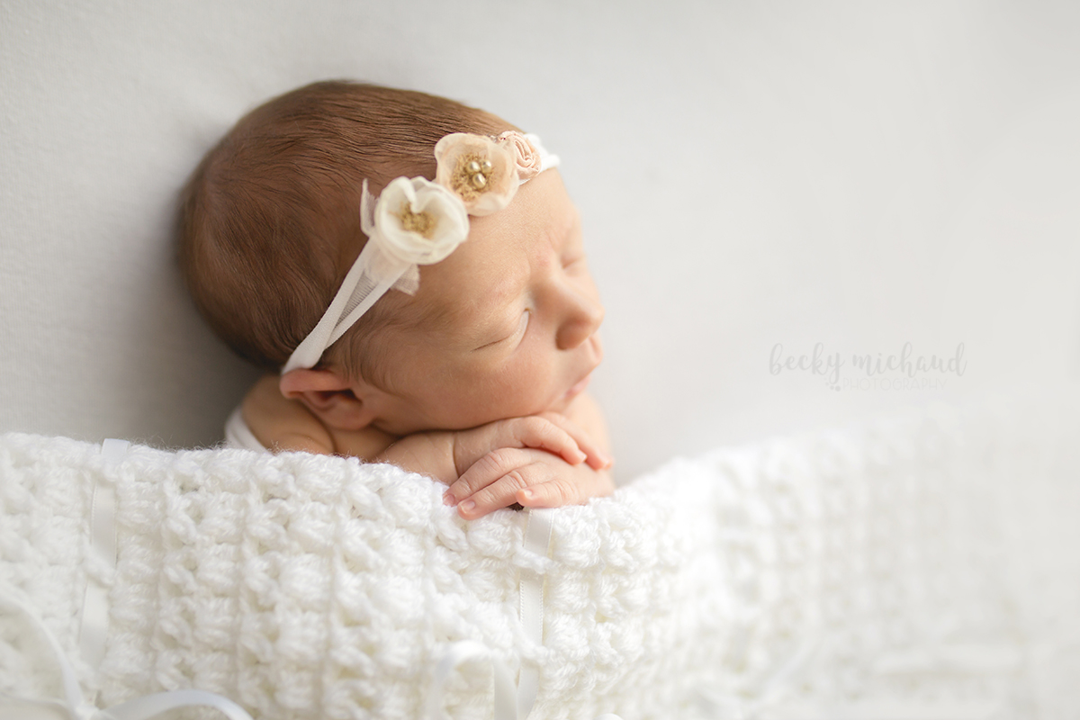 A baby girl sleeps under a white heirloom blanket