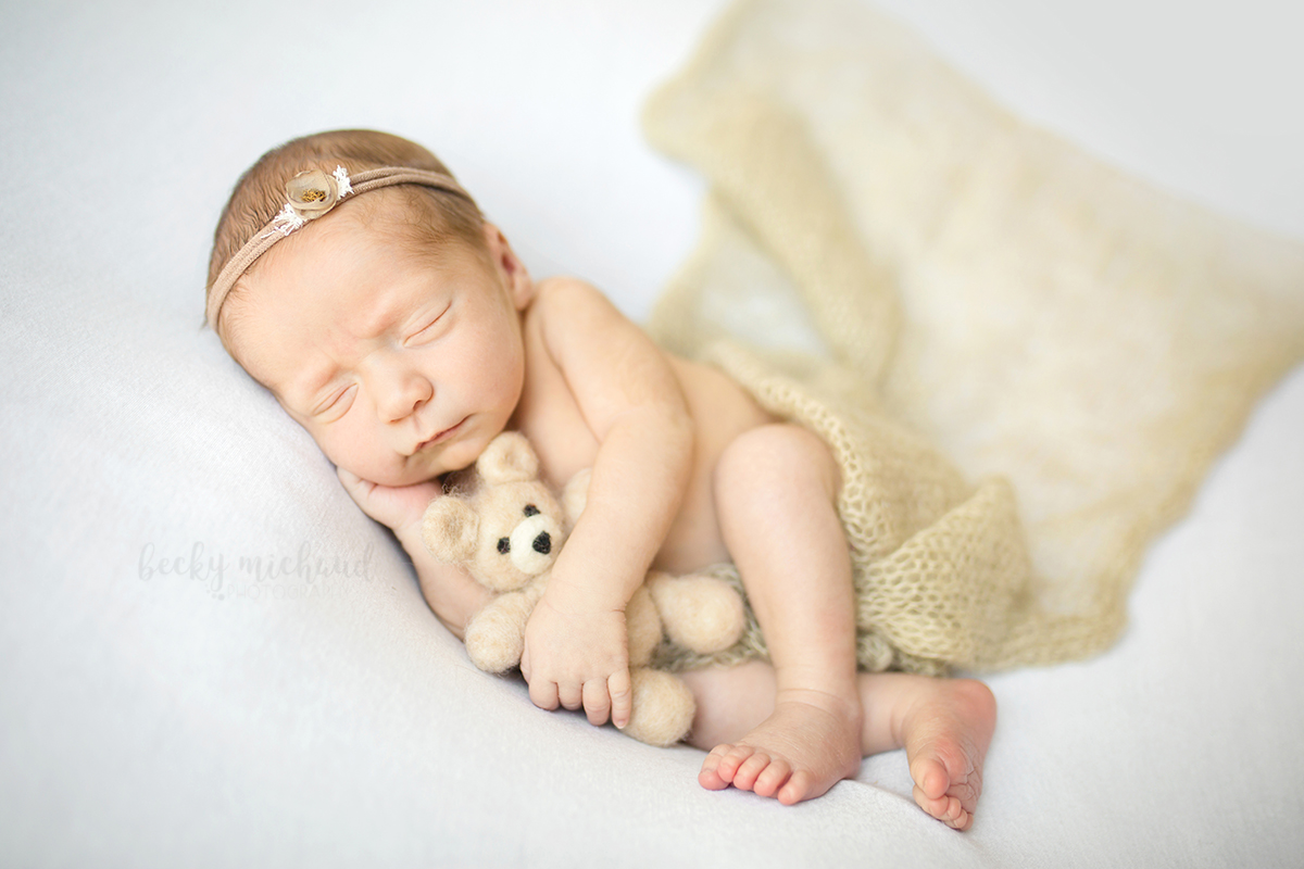 Organic newborn photo of a baby girl holding a teddy bear taken by Becky Michaud, Fort Collins Photographer