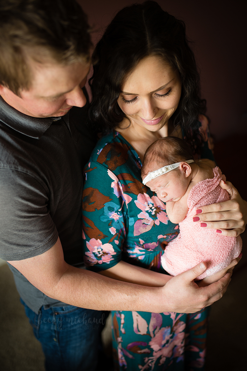 Parents pose with their newborn girl during their Northern Colorado photo session