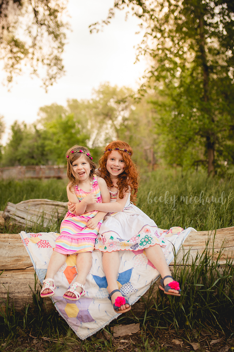 Two girls sit on a log and hug each other during their Fort Collins family photo session