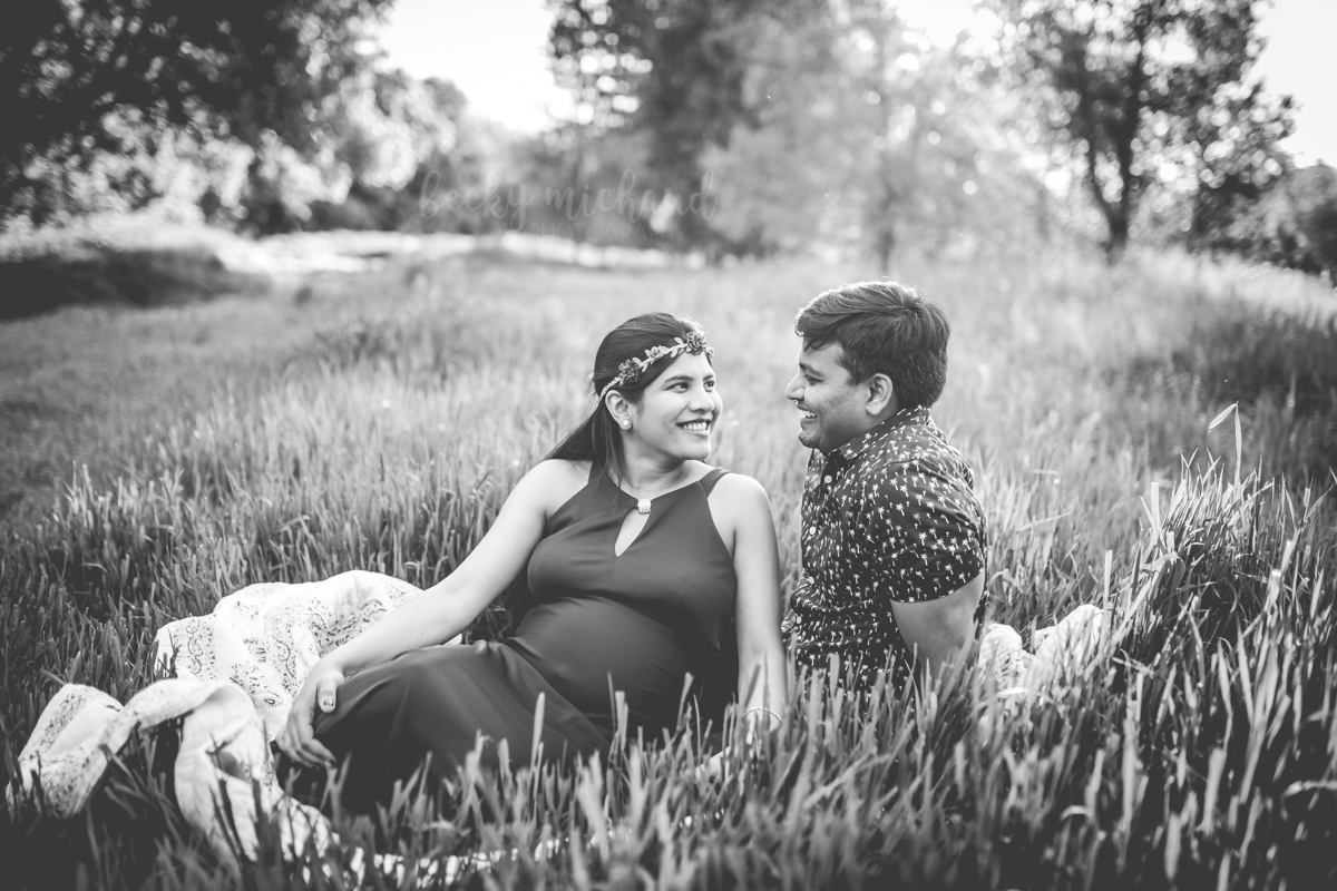 Black and white photo of a couple sitting on a blanket during their maternity photo shoot