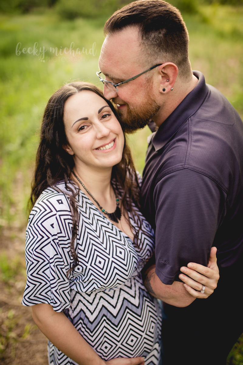 A man kisses his wife's head during their Fort Collins maternity photo session