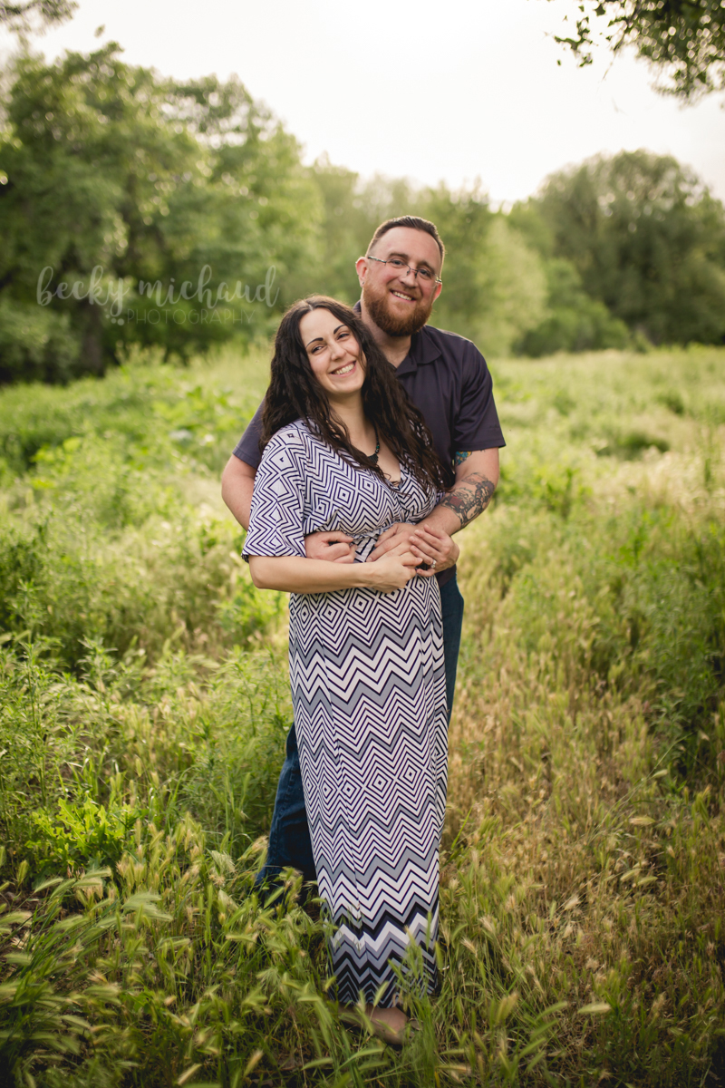 A couple stands together at Legacy Park in Fort Collins during their maternity photo session