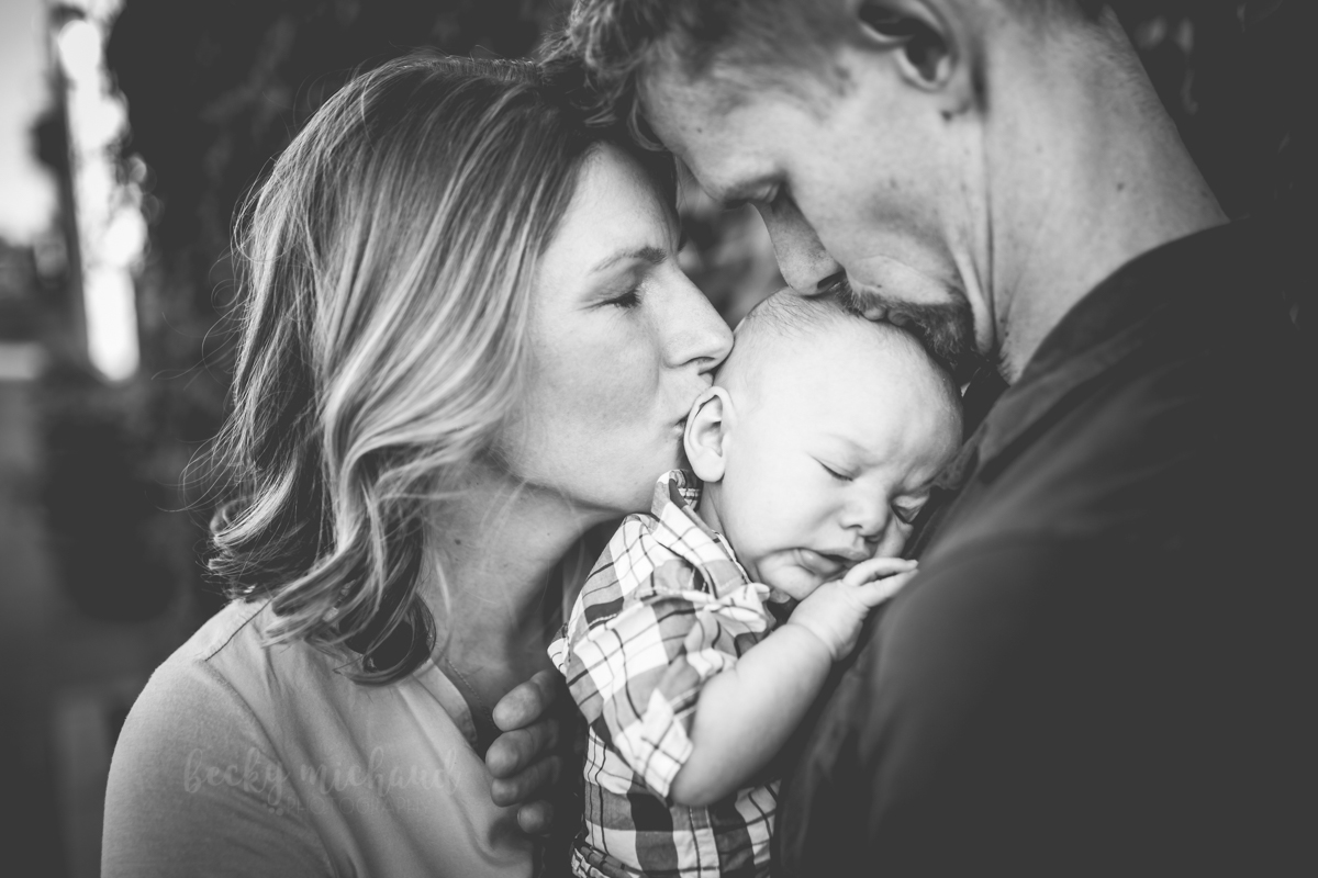 Black and white photo of a mom and dad kissing their baby boy during their outdoor family photos