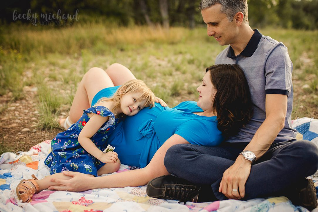 maternity photo of a family reclining on a blanket together at a Fort Collins Natural Area