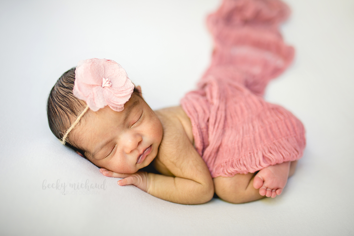 A baby girl in pink sleeps on a white backdrop during her in home newborn photography session