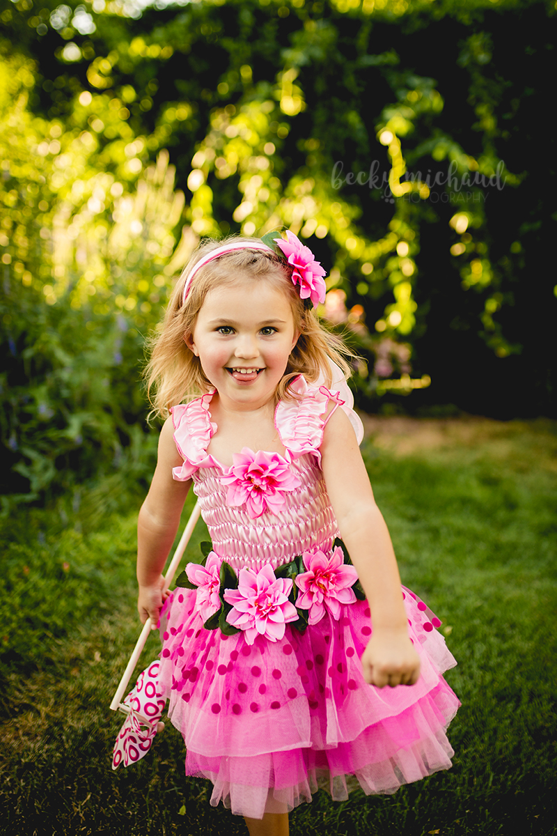 A little girl in a pink fairy costume runs happily toward her photographer at a Colorado flower garden