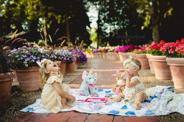 Two little girls having a tea party in a flower garden in Fort Collins Colorado