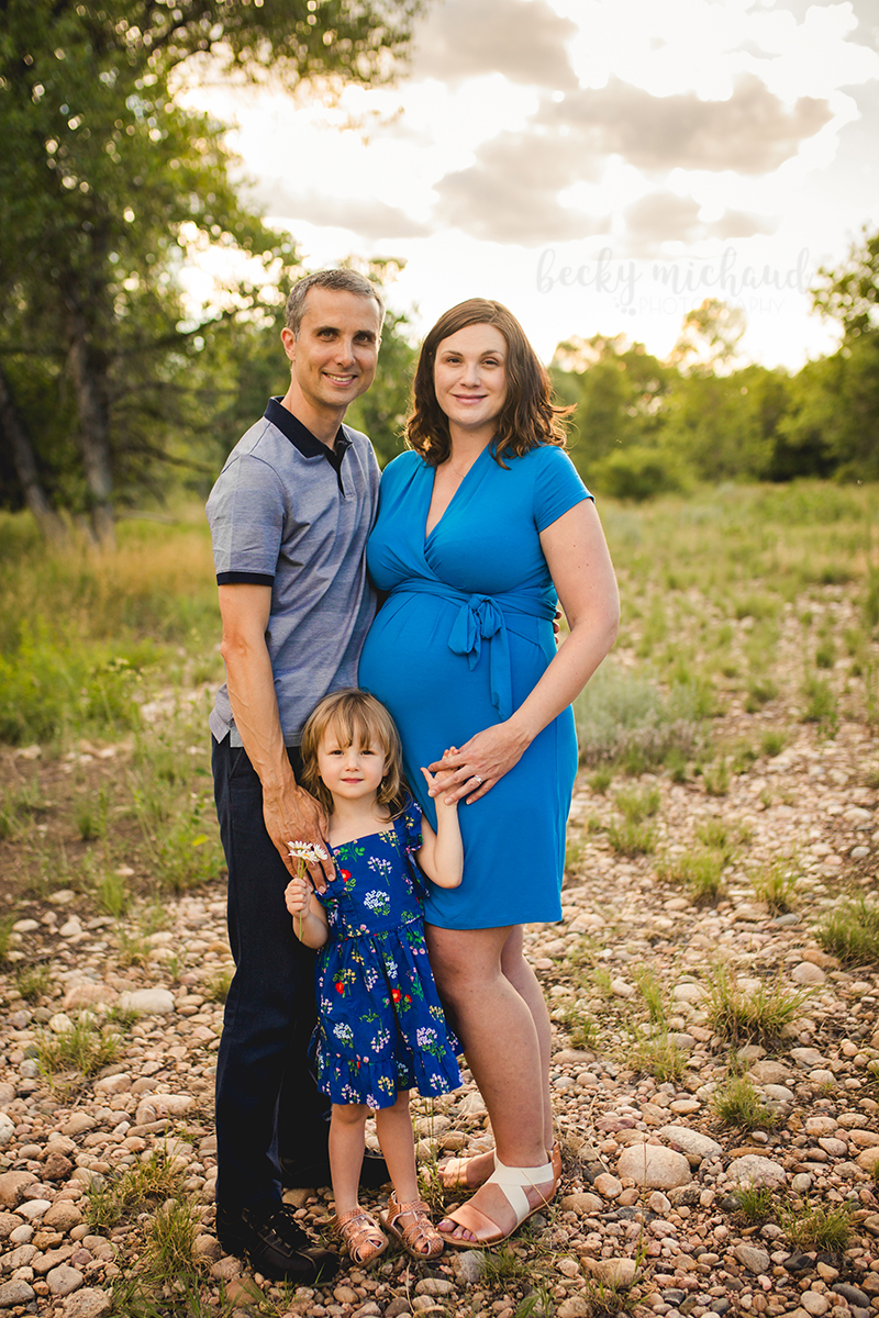 A family of three poses at Legacy Park in Northern Colorado for their maternity portrait shoot
